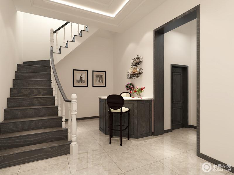 设计师在楼梯下方布置了吧台,弧形的吧台以木质结合大理石,硬朗朴厚的材质呼应着楼梯的阶梯,视觉上平衡素雅;高脚椅流线优美,闲趣的配搭在吧台两侧,花卉和画作的装点,为空间点缀出浪漫休闲。