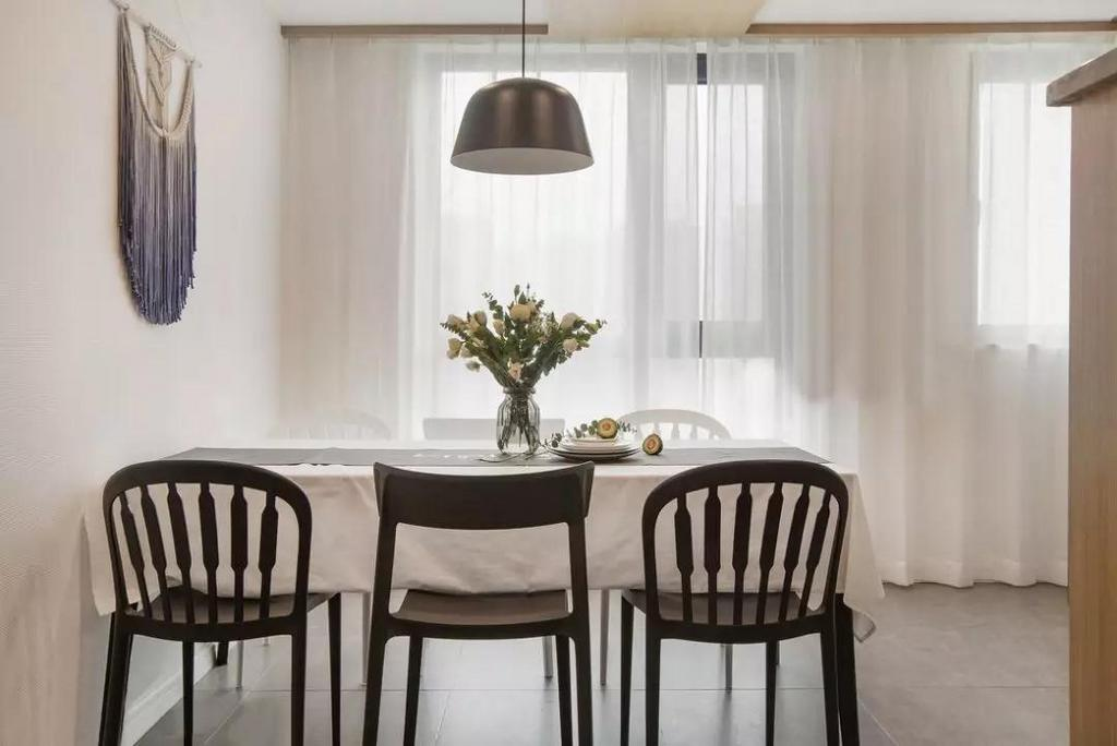 餐厅一张木质餐桌搭配黑白双色餐椅,干净清爽的白色桌布和轻盈的窗帘相互呼应,吊灯及渐变编织挂毯增添层次提升空间格调。
