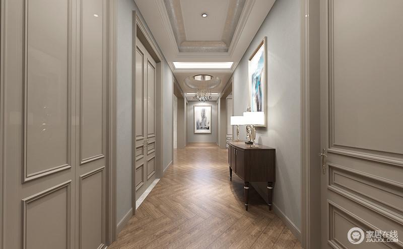 深且长的走廊,两侧墙面以浅灰蓝配灰褐色,门框丰富的简洁线条勾勒出墙面的雅致气质。玄关背景以褐色边几配墨染挂画演绎,挂画与端景墙上水墨,形成遥相呼应之势。