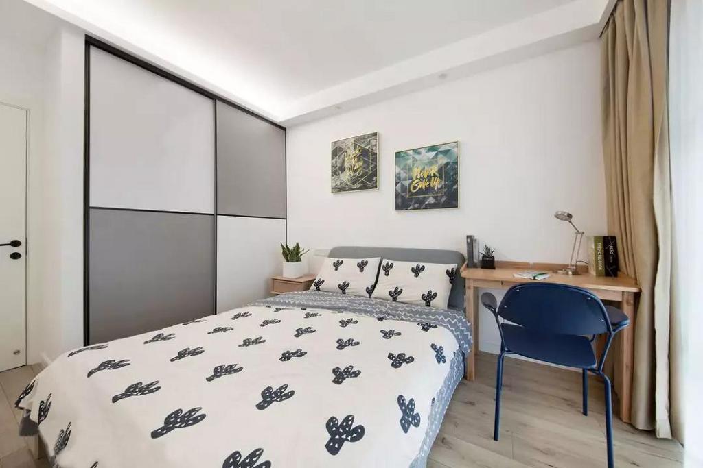 次卧以灰白两色为主调,衣柜柜门的巧妙设计增强空间层次感的同时,也带来了一定的趣味性。临窗设置书桌区域,深蓝色单椅进行点缀,沉静而复古。