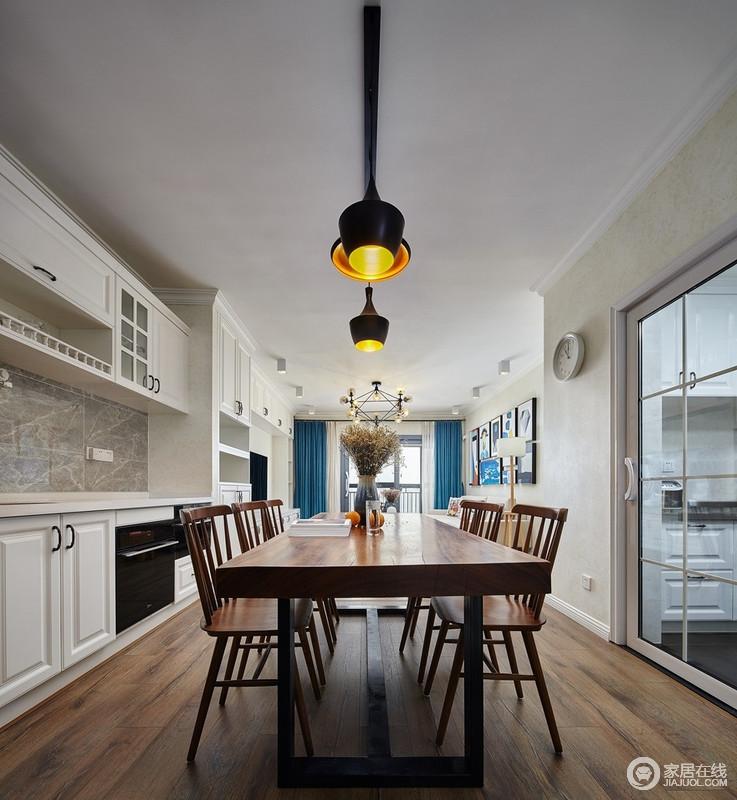 餐厨一体式空间,胡桃色实木餐桌搭配餐椅,赋予空间稳重和温馨;餐厅吊灯投射出温暖的光影,带着工业设计的大气,让生活充满了温馨;而白色橱柜搭配灰色墙砖,实用、素静,让空间足够得体。