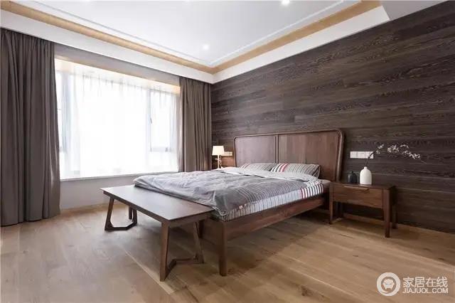 卧室的背景墙铺贴了深灰木纹砖与胡桃木床、床头柜、与床尾凳,形成朴质和温实,颇具质感;简约素雅的床单窗帘布置,营造出一种端庄舒适的氛围,极具中式和静。