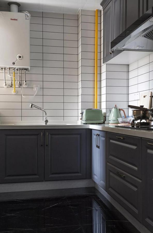 厨房以灰白两色为主调,灰调一体式橱柜、白色的操作台,还有黑色大理石纹路地砖,简约至上,又不失时尚感。