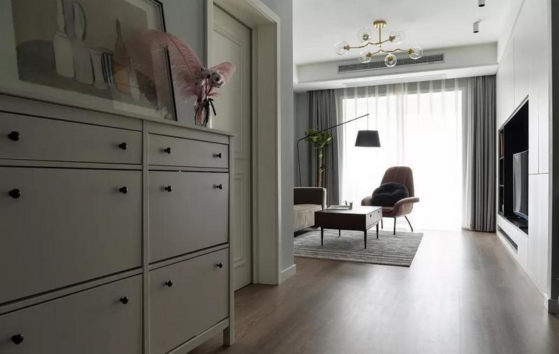 进门左侧设置小矮柜作为简易鞋柜与端景台,摆放装饰画与轻盈的粉色羽毛摆件,打造浪漫而又惬意的入户空间。