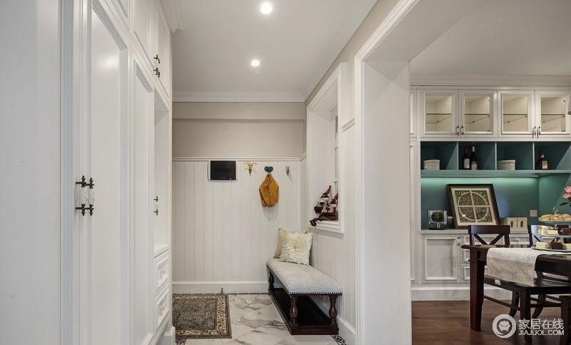 进门处有玄关设计,方便客人换鞋和放置衣服,板材板材搭配储物柜,让整体设计更为精致,再加上衣钩和坐凳,十分人性化。