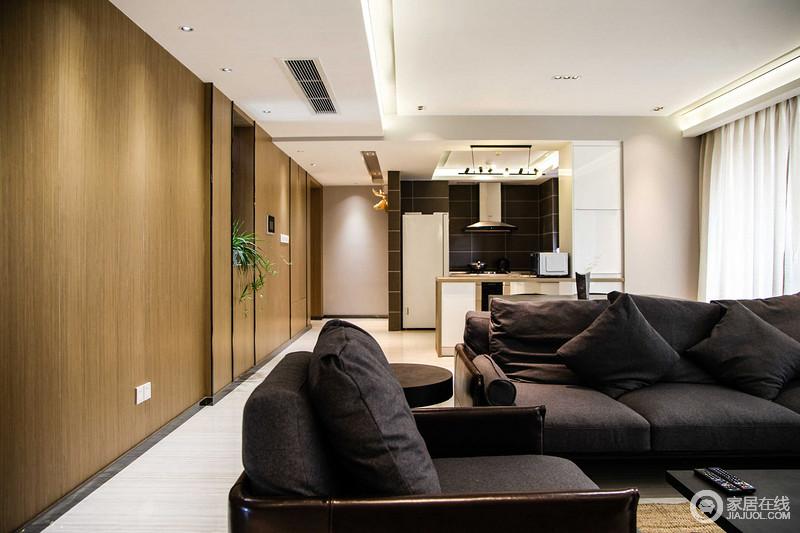 客厅与厨房吧台一体式设计让原本的空间更为简洁实用,动线自然分区,起到分区的作用;黑灰色的布艺沙发搭配黑色茶几,延续现代利落。