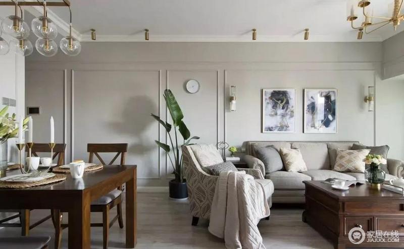 餐厅和客厅之间是没有做隔断的,墙面都是简单的做上石膏线边框,沙发背景墙上方有着挂画和壁灯作为点缀,加重了中性灰色的时尚感,令空间愈加温和安适。