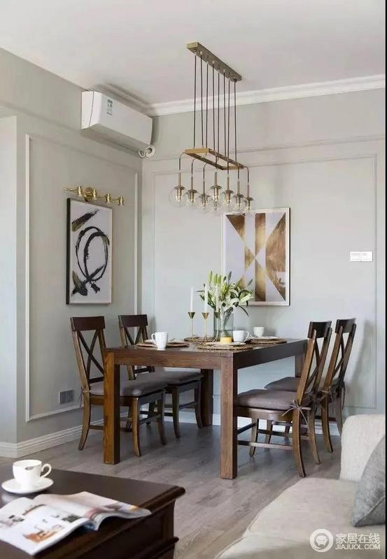 餐厅背景墙的设计和沙发背景墙基本上相同,也刷成了浅灰色更有整体感;美式风的木质餐桌椅更为沉稳大气,搭配两幅风格迥异的艺术挂画和金属灯饰,装饰出美式现代艺术,厚重而轻奢。