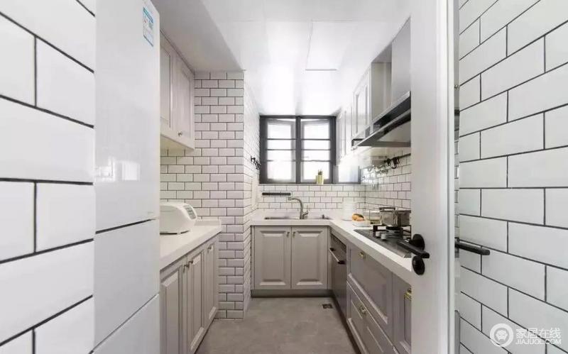 厨房内部是一个狭长的形状,橱柜做了L形与一字形的设计,满足不同的操作使用,工字铺贴的小白砖和灰色调的橱柜、水泥质感的地面结合,看起来非常朴质。