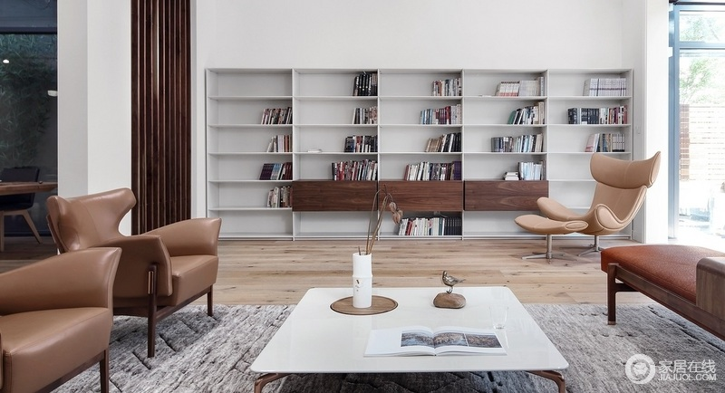 设计师改变了原有的客厅电视背景墙,变成了一个阅读区,白色的书柜不喧宾夺主,却让整个空间干净,沉稳;褐色木柜立面的装饰,起到了平衡的作用,让立面具有收纳美学,并与旁侧的扶手椅,组成生活的温情。