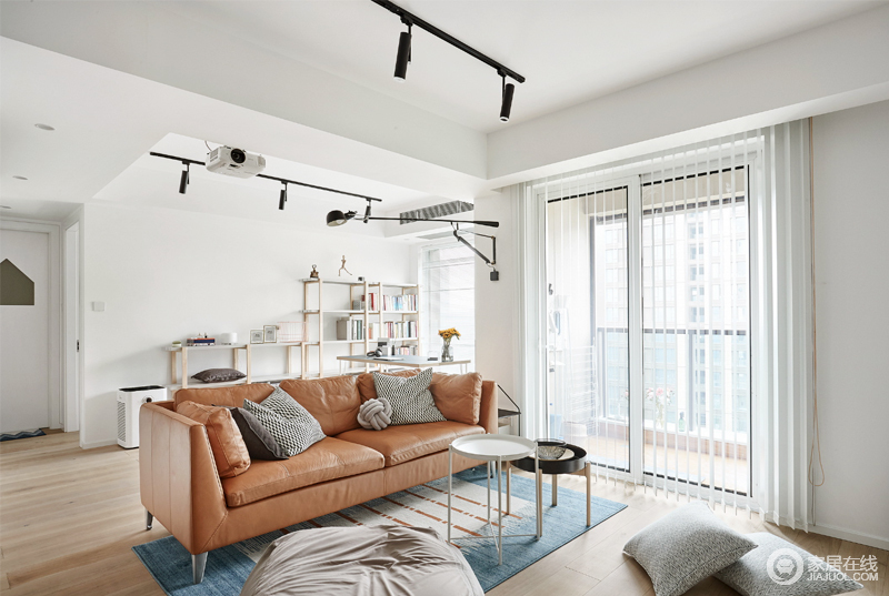 白色的空间采光充足,客厅区的褐色皮质沙发搭配小圆几十分轻和,而读书区的简约木书架,给主人一个独有的空间。