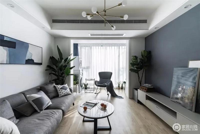 客厅打通了阳台,令空间的采光很好,而灰蓝色的电视背景墙搭配白色吊顶与白色主墙,整体清爽和谐,木色地板造就大气自然简单的空间格局,让生活富有品味。