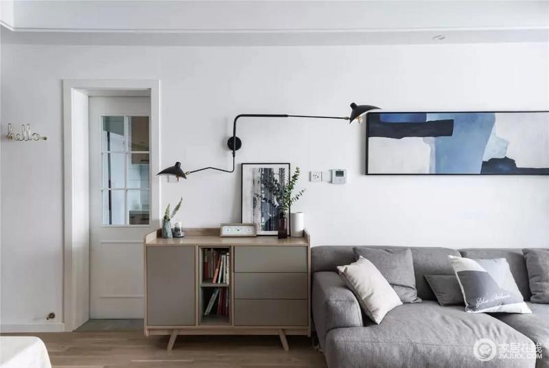 沙发背景墙也比较简洁,一幅跟灰蓝色墙面对应的水彩画用作装饰,搭配工业风十足的壁灯,照顾不同方位的采光需求,与边柜上的画作和花艺凑成清和、艺术格调。