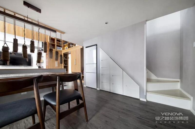 在沙发背景墙的后方就是餐厅空间,半墙加上隔断的设计,让空间更显通透。楼梯底部的空间也没有浪费,冰箱加上储物柜,满足餐厅需求。