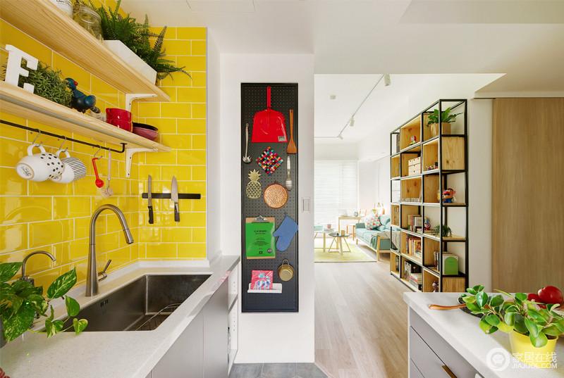 厨房以简单的U型设计将洗菜区和烹饪区分开,浅灰色的橱柜搭配明黄色的瓷砖,让空间明快艳丽,而实木支架实现了空间的储物功能,简单大气,黑色挂区上的日常之物成为空间的点睛之处,也绽放着童趣。