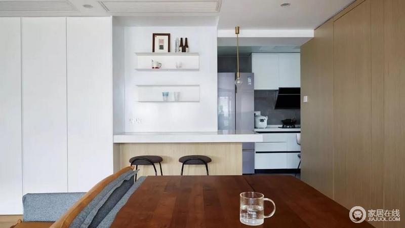 厨房在简餐区的一侧,白色柜体搭配灰砖,色调与整室和谐统一,小型吧台与悬挂式储物格,让生活极具实用性。