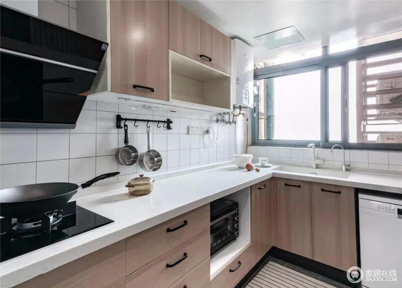 厨房以白色文化砖搭配木色橱柜,多了北欧的温实;L型一体式橱柜嵌入烤箱,让生活十分便利;黑色把手搭配白色台面,配以白色墙砖,空间明亮干净。