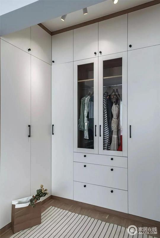 衣帽间U型的衣柜格局将空间利用到极致,一体式的墙面柜大大增强每个部位的储物能力,白色的柜面的玻璃门增添了明亮通透感。