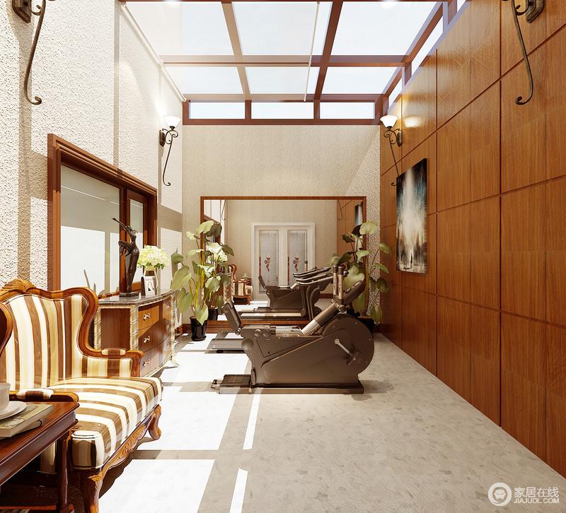 健身房在顶层,玻璃吊顶增加了整个空间的采光和通透性,搭配粗粝感的墙面,有种回归田园的朴质和惬意;健身器材是主要设备,但是为了休闲专门配置了美式沙发椅,供主人休息之用,再加上整体性衣柜,让空间实用与美学并重。
