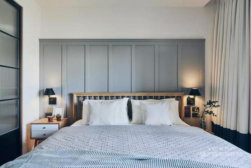 卧室床头背景墙是以蓝灰色护墙板的装饰,搭配木架床铺与简约舒适的床单,整体空间显得充满舒适自然的氛围感。旁边窗外也是有着宽敞明亮的视觉与光线感。