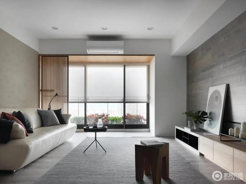 客厅从左到右分别是暖灰色的沙发墙,布置舒适的米白色皮沙发,中间的茶几尺寸较小,留空出宽裕的活动空间垫上灰色地毯,在大面落地窗的百叶帘采光下,显得充满明亮舒适的大方感。