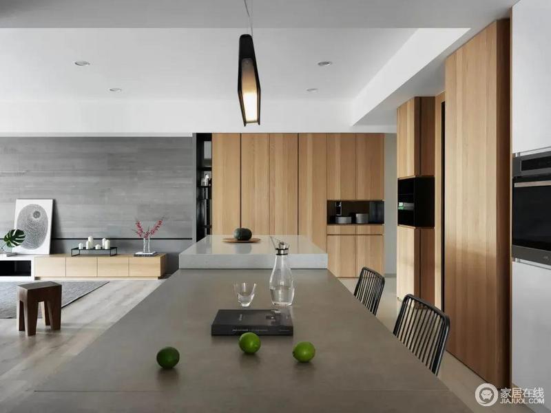 餐厅区域布置灰色台面的餐桌,旁边挨着一个白色大理石台面的中岛台,侧边木质的电器柜布置,整体空间显得简约自然而又温润大气。