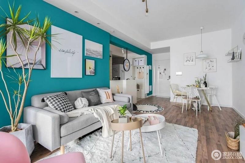 客厅湖蓝色的背景墙搭配简画,清新而活力,灰色沙发搭配白色地毯和北欧风的圆几,让空间轻快之余,富有生活格调。