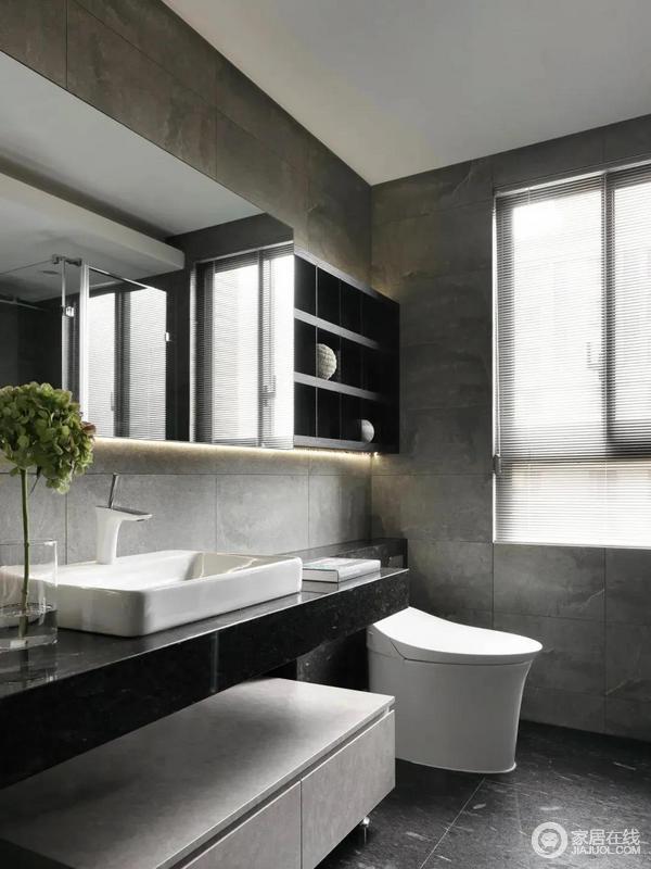 卫生间整体是灰色的空间感,搭配黑色的洗手台台面与台上盆设计,而洗手盆后方的镜柜,也设计延伸到马桶后方,让空间收纳更加实用方便。