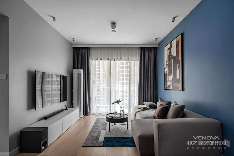 客厅在灰色电视墙+蓝色沙发墙,搭配木质地板,整体简约自然的家具布置,营造出一种现代轻松的大气。