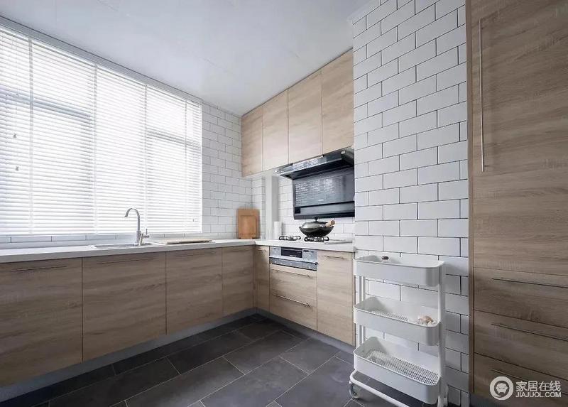 设计通过玻璃门将厨房和餐厅隔开,玻璃门阻挡了油烟的蔓延,又保证了厨房的采光通透性;厨房白色文化砖与灰色地砖形成色彩上的反差,让空间更有层次,而原木定制橱柜足显北欧的生活暖意。