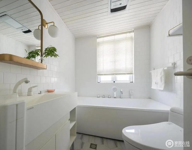 """白色的卫生间整洁干净,纯白的洗手台金边挂镜,架子上放了一盆绿植作为装饰,摆放在这里旁边还有一个同色的小壁灯用来补充照明,可谓""""精致与实用""""并存。"""