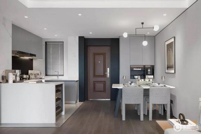 进门右手边是厨房,开放式的设计更显宽敞,左手边是餐厅,定制的厨柜为生活增加了储物空间,更为实用;简约的吊灯、个性的餐椅赋予空间都市生活气息。