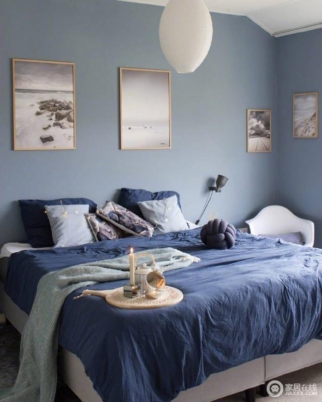 卧室以蓝色漆粉刷,配以各类风景挂画,凸显出一种文艺和宁静;深蓝色床单与墙面构成反差,却柔软、舒适。