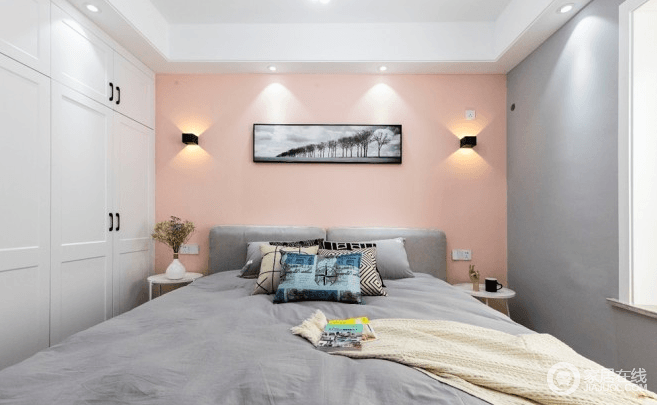 床头正面,配色延续了客厅的配色,高级灰和粉橘的搭配,让人心情愉悦;灰色布艺床,挑选的颜色接近乳胶漆的颜色,而白色铁艺床头柜简洁实用,两个壁灯也都是单独控制, 而且特地选3000k色温的灯光,相对亮度低,不会刺眼,让生活保持健康。