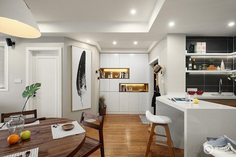门厅的白色定制柜解决了收纳的问题,同时让这个不太规则的空间不失实用性;玄关柜的展陈架减少了平淡,强调几何效果,同时借一副黑色羽毛的挂画,演绎黑白美学,射灯渲染了一篇通明。