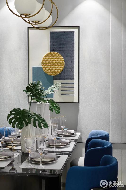 餐桌上精致的餐具、酒杯与花瓶,布置出一种雅致温情的用餐氛围感;原本灰色的空间,因为蓝色法兰绒的搭配,柔和之中,多了现代贵气。