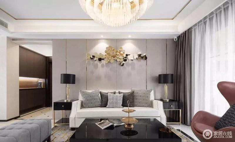 客厅背景墙金色配饰丰富空间层次,再加上金属质感的台灯、桌几呈对称陈列。装点出优雅格调便跃然纸上;白色铆钉美式古典沙发搭配灰色长椅、黑色茶几以经典之色,组合出古典时尚,水晶灯更是增添华贵。