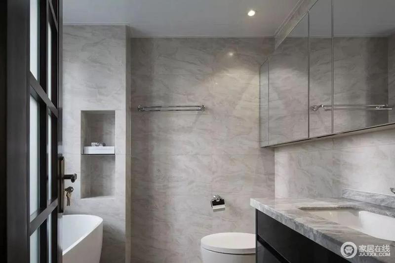 卫生间以灰色为基调,大面积的镜柜提供强大收纳功能的同时带来延伸空间视觉的效果。临浴缸一侧的墙面设置壁龛,兼具实用性和美观性,更为规整得体。
