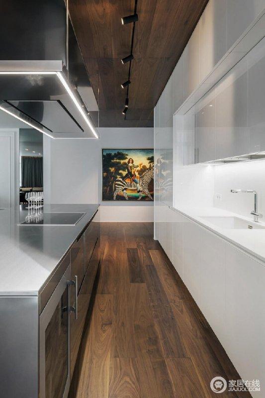 开放式客餐厨的格局配置加深了视觉通透感,大片落地窗不仅引光线入内照亮整个空间,也让城市景观尽收眼底;白色橱柜搭配褐黄色木地板,构成现代利落和大气。