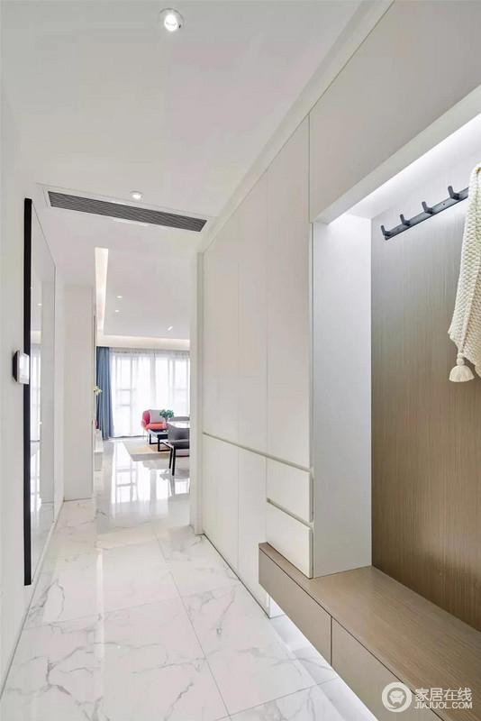 玄关的地面与客厅延续整体雅白的色调,定制的一体式白色鞋柜,与木色换鞋凳抽屉搭配设计,显得简洁大气,不失自然朴质。