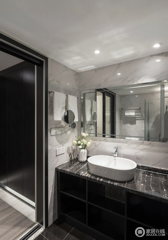 卫生间白色瓷砖铺贴墙面,却将黑灰色台面和盥洗柜连为一体,形成空间的黑白反差之美,搭配镜面收纳柜,在保证实用之余,成就空间的高级感。