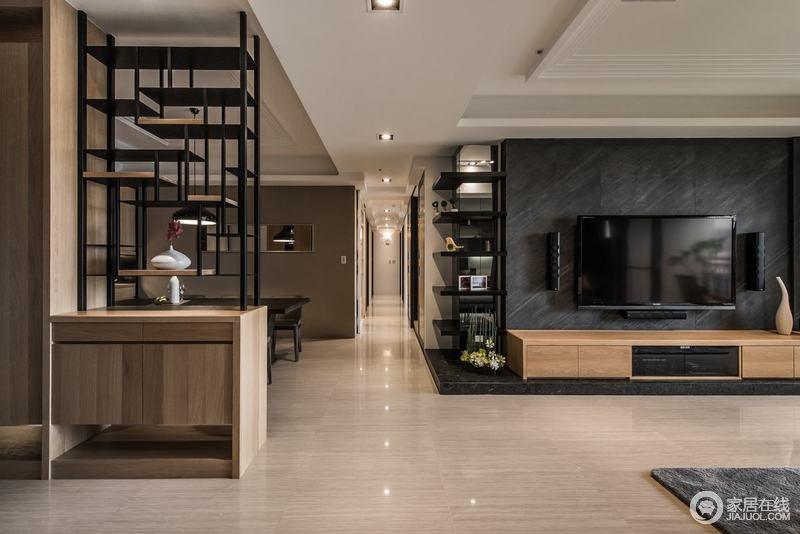 空间并没有太多明确的划分,却通过走廊做简单区分,同时以动线突出规划设计感;黑色大理石背景墙与木纹地砖构成空间的层次,黑色几何书架和木柜巧妙满足实用,同时与玄关柜构成呼应,让几何设计带来简约之美。