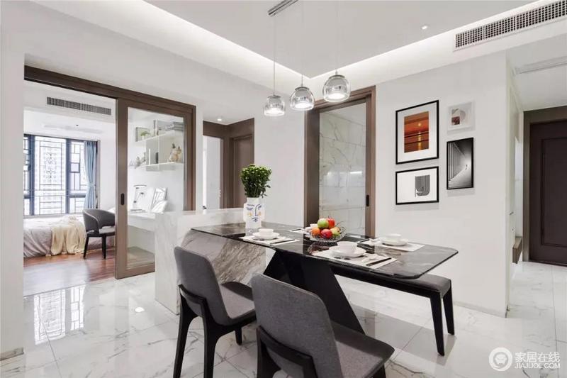 餐厅的餐桌是黑色大理石质感,墙搭上灰黑配的餐椅,靠着一个中岛台布置,让空间实用又时尚;墙面的挂画提升了空间的艺术气息,与银色吊灯的时尚,碰撞出空间的精致。