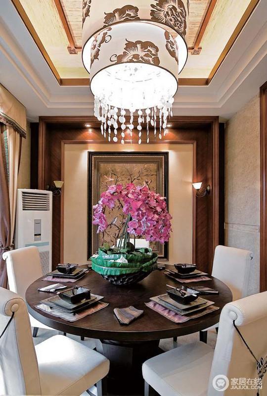 餐厅吊顶和挂画以花卉色元素来表达热带风情,灯带和吊灯组合,彰显奢华;圆桌旁的布艺餐椅带着现代设计,粉花渲染,满是惬意。
