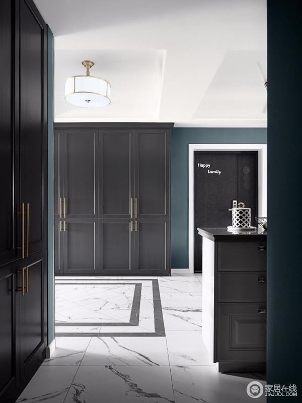 过道沿着墙体设计了一排暗色系柜子,与整屋协调统一,增加家中的收纳,同时,搭配灰色地面,给予空间深色系的稳重。