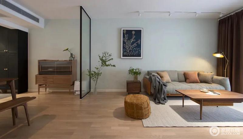 客厅通铺浅色木纹地板与茶几、胡桃木斗柜呈木调之风,浅灰色沙发与浅绿色背景墙成柔和,为空间赋予色彩之外,因绿植的点缀摇曳生姿,充满生活的味道。