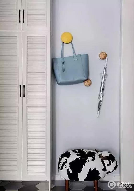 入户玄关木作60公分深的厚柜子,除了能够收纳不常穿的鞋子,还能收纳行李箱等杂物,钮扣衣帽钩与小牛换鞋凳增添空间趣味性
