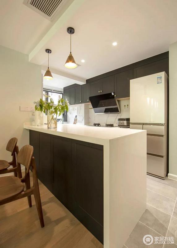 小吧台是客餐厅的隔断,地面的铺设也不相同,从地板到瓷砖的过渡,起到划分空间的作用;吧台和地柜连成U字型让厨房有了充足的操作与收纳空间,十分自在。