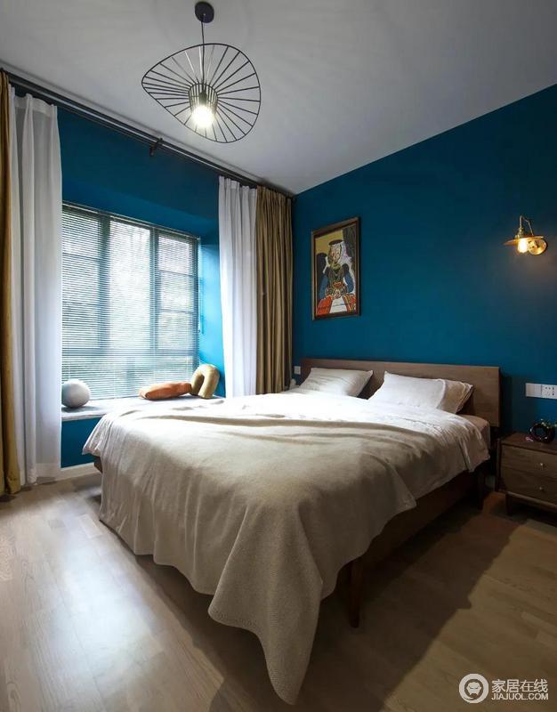 主卧墙面的深蓝色和胡桃木的家具搭配在一起呈现自然、复古的格调;飘窗的白色纱幔与之呈现蓝白之美,颜色的挂画、明黄色的靠包和米驼色的窗帘又赋予空间色彩活力,满是温馨。