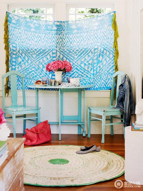 客厅靠窗处,专门打造了一个极具时尚感的休息区,蓝色木质圆桌和椅子清雅而实用,搭配蓝色几何窗帘、草毯,构成田园般惬意生活。